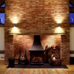 Large traditional fireplace with lighting by Sam Coles Lighting