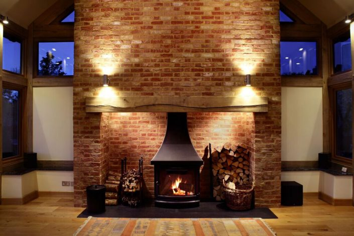 Large fireplace with lighting by Sam Coles Lighting